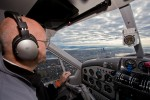 Pilot Doug DeVries takes the plane over downtown Seattle on approach to KBFI. (Photo by John Harrell)